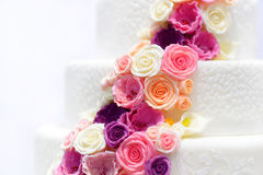 Gâteau de mariage blanc décoré des fleurs de sucre Images stock