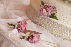 Gâteau de mariage blanc décoré des fleurs et de l'ensemble de coupeurs Images libres de droits