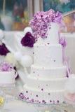 Gâteau de mariage blanc décoré des fleurs pourpres Photographie stock libre de droits