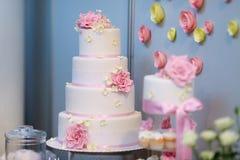 Gâteau de mariage blanc décoré des fleurs roses Images libres de droits