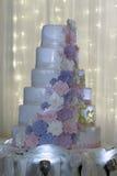 Gâteau de mariage blanc de niveau multi avec les fleurs roses Images stock