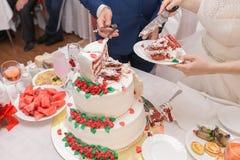 Gâteau de mariage de coupe de jeunes mariés Photographie stock libre de droits