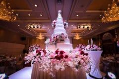 Gâteau de mariage et décorations de fleurs avec le lustre sur le plafond Image libre de droits
