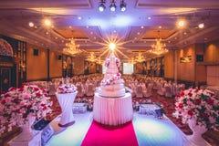 Gâteau de mariage et décorations de fleurs avec le lustre sur le plafond Photo libre de droits