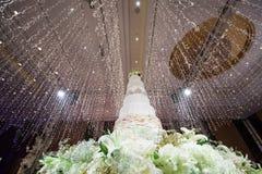 Gâteau de mariage floral blanc sur le fond d'éclairage d'hôtel Image stock
