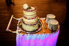 gâteau de mariage Multi-à gradins avec les canneberges et la rose de blanc en haut, sur le chariot, couteau, plats Image stock