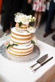 Gâteau de mariage de niveau multi avec des fleurs sur la table Images libres de droits