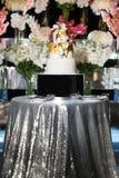 Gâteau de mariage de niveau multi avec des fleurs sur la table argentée Photo libre de droits