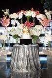 Gâteau de mariage de niveau multi avec des fleurs sur la table argentée Image libre de droits