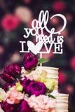 gâteau de mariage Trois-à gradins décoré de belles fleurs et d'inscription en bois Images libres de droits