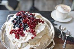Gâteau de meringue avec des baies sur un plateau argenté et une tasse de café images libres de droits