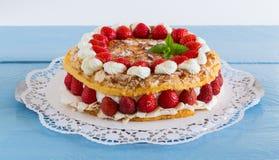 Gâteau de meringue avec du yaourt de fraise sur le bois bleu Photo stock