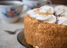 Gâteau de miel avec des fleurs et thé sur la table, couverte de toile de jute Photo libre de droits
