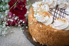 Gâteau de miel avec des fleurs et thé sur la table, couverte de toile de jute Photographie stock libre de droits