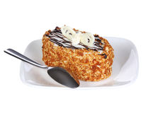 Gâteau de miel délicieux avec du chocolat sur le dessus avec la cuillère du plat, d'isolement sur le blanc. Nourriture russe image libre de droits