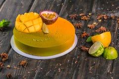 Gâteau de mousse de fruit avec une mangue et un décor de litchi sur un support en bois images libres de droits