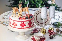 Gâteau de Noël blanc avec l'ornement rouge sur supérieur décoré des chiffres de mastic des cerfs communs et des baies fraîches su Photographie stock libre de droits