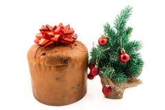 Gâteau de Noël de Panettone avec le fond de blanc de décoration de brin de feuille de cyprès de signe, de houx, de gui, de lierre Images stock