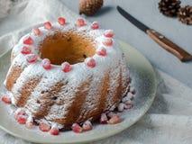 Gâteau de Noël sous forme de guirlande avec les graines en poudre de sucre et de grenade sur un foyer sélectif de plat blanc Images stock