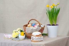 Gâteau de Pâques et le bascket avec les oeufs colorés et les fleurs jaunes, sur la table image libre de droits