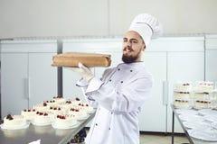 Gâteau de participation d'homme de confiseur souriant dans un magasin de pâtisserie photographie stock libre de droits