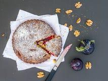 Gâteau de prune avec des noix sur un morceau de livre blanc sur le noir Photos libres de droits