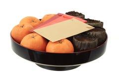 Gâteau de riz d'an neuf et mandarines chinois Images stock