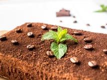 Gâteau de tiramisu avec les grains de café et le chocolat de menthe fraîche sur le conseil dans la fin blanche de fond  Photo stock