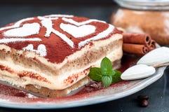 Gâteau de tiramisu d'un plat gris décoré des coeurs de sucre en poudre Image libre de droits