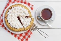 Gâteau doux décoré de la meringue et de la tasse de thé Photographie stock libre de droits
