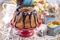 Gâteau doux fait maison, versé avec du chocolat, d'un plat rouge de gâteau Sur un fond en bois brun, des herbes sèches pour le th Image stock