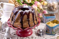 Gâteau doux fait maison, versé avec du chocolat, d'un plat rouge de gâteau Sur un fond en bois brun, des herbes sèches pour le th Images stock