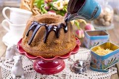 Gâteau doux fait maison, versé avec du chocolat, d'un plat rouge de gâteau Sur un fond en bois brun, des herbes sèches pour le th Photos libres de droits