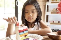 Gâteau eatting de fille asiatique en café photos stock