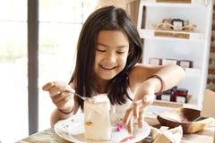 Gâteau eatting de fille asiatique en café images libres de droits