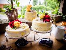 Gâteau et bonbons de mariage blanc décorés des fleurs naturelles Photos stock