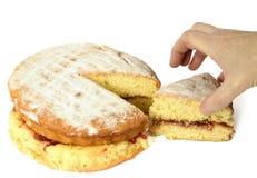 Gâteau et main Photographie stock libre de droits