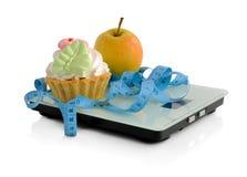 Gâteau et pomme sur des échelles mesurant la bande enveloppée Photos libres de droits