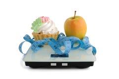 Gâteau et pomme sur des échelles mesurant la bande enveloppée Photo libre de droits