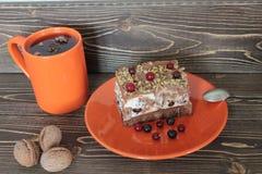 Gâteau et thé avec des herbares dans une tasse orange Image stock