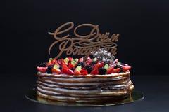 Gâteau fait maison de biscuit avec de la crème et des baies sur le fond noir Photo stock