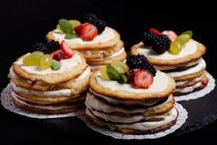 Gâteau fait maison de biscuit avec de la crème et des baies sur le fond noir Images libres de droits