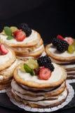 Gâteau fait maison de biscuit avec de la crème et des baies sur le fond noir Photos libres de droits