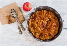 Gâteau fait maison de pomme et de cannelle Tarte dans le plat de cuisson, la fourchette de vintage et la cuillère et le fruit fra Images stock