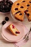 Gâteau fait maison de prune sur un support en verre et des plats roses Photos libres de droits