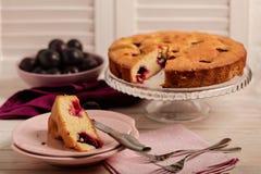 Gâteau fait maison de prune sur un support en verre et des plats roses Image stock