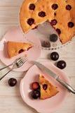 Gâteau fait maison de prune sur un support en verre et des plats roses Image libre de droits