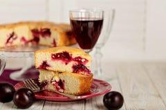 Gâteau fait maison de prune sur un support en verre et un vin rouge Images libres de droits
