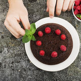 Gâteau fait maison fou de chocolat décoré des framboises par les mains masculines sur un fond gris Vue supérieure Images libres de droits