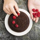 Gâteau fait maison fou de chocolat décoré des framboises par les mains masculines sur un fond gris Vue supérieure Images stock